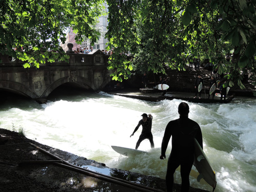 "Surfers at the ""standing wave"" in Munich's English Garden"