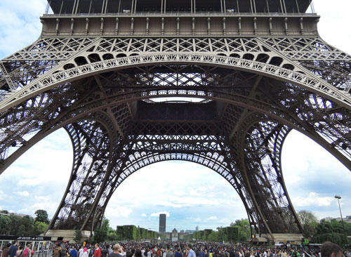 The massive legs of the Eiffel Tower along with the massive crowd.